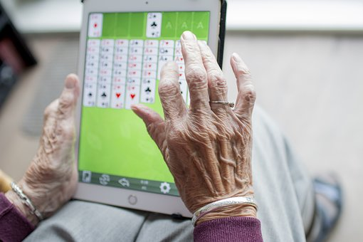 elderly lady in care home using technology for activities card game
