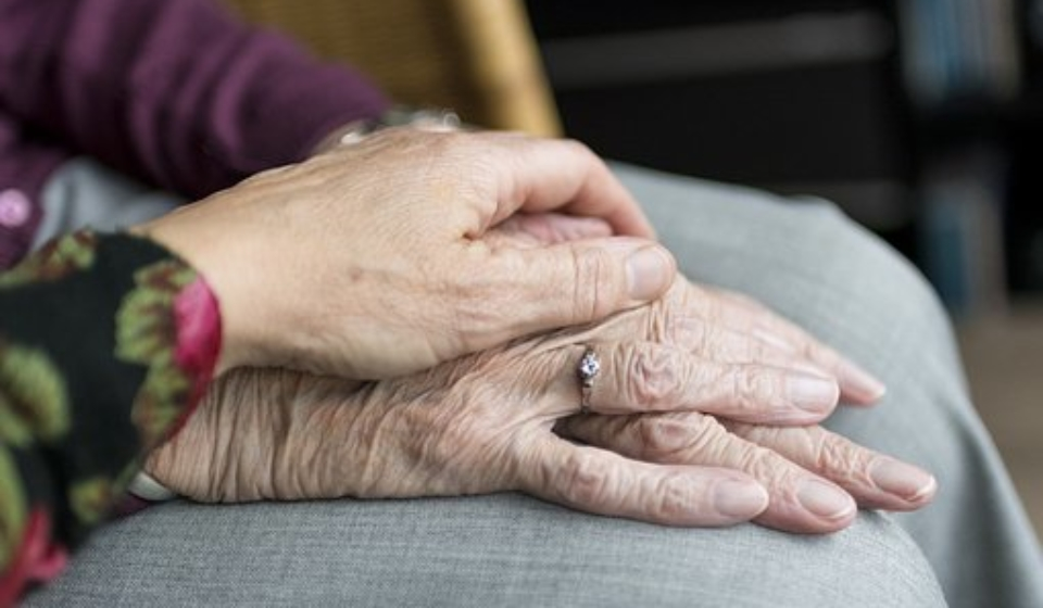 elderly eoman in care home with help from staff holding hands